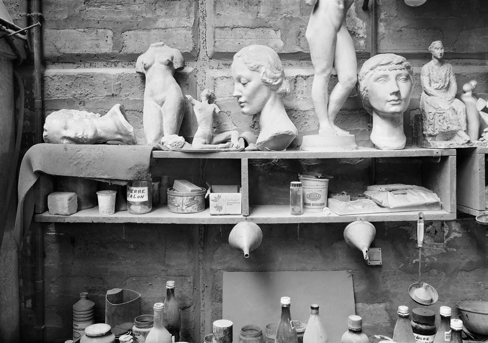 Sculptures of busts and body parts sitting on a shelf, in black and white