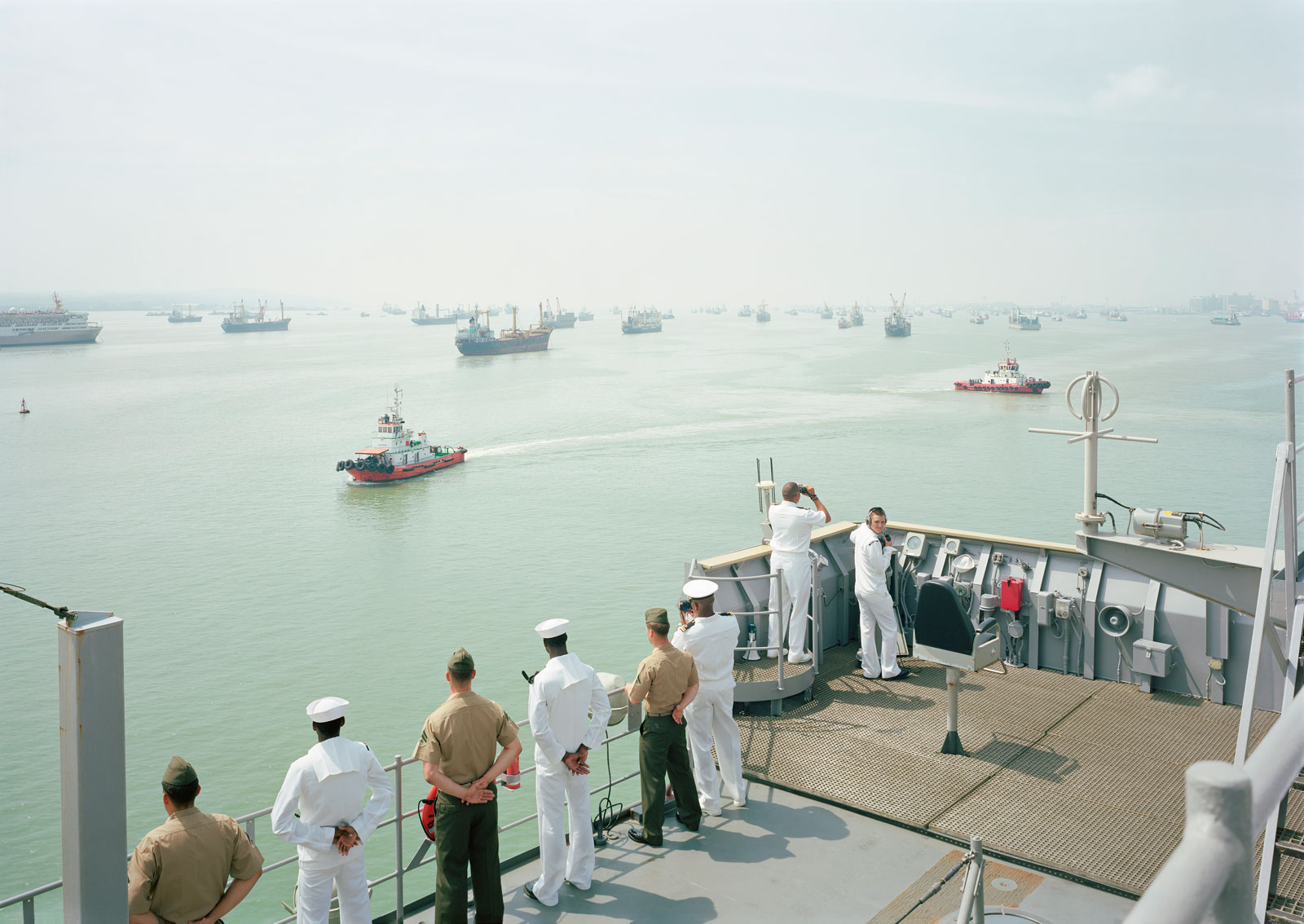 Sailors looking from the dek of a ship out onto the water, where other ships are parked