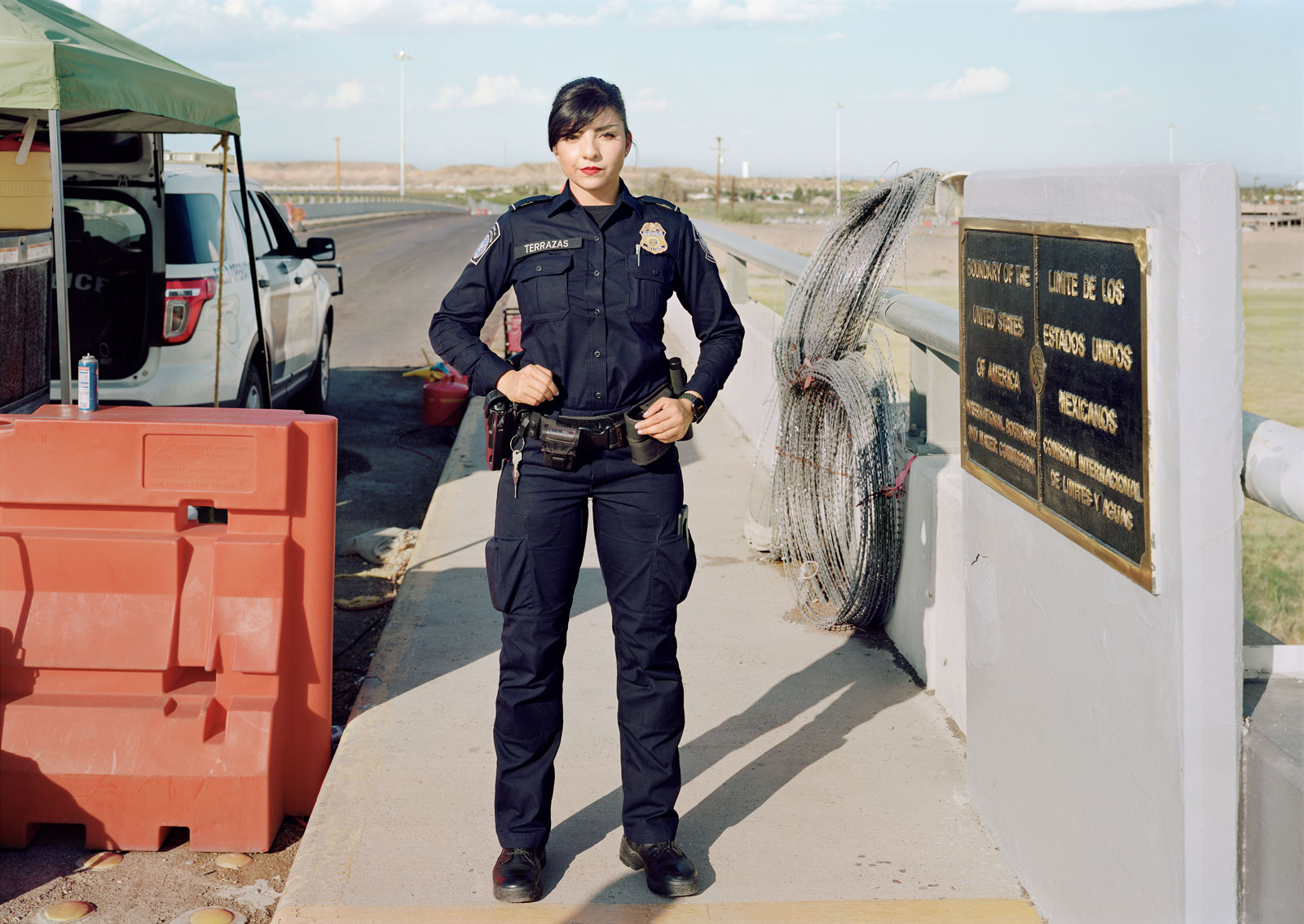 A woman in uniform stands with hands on hips