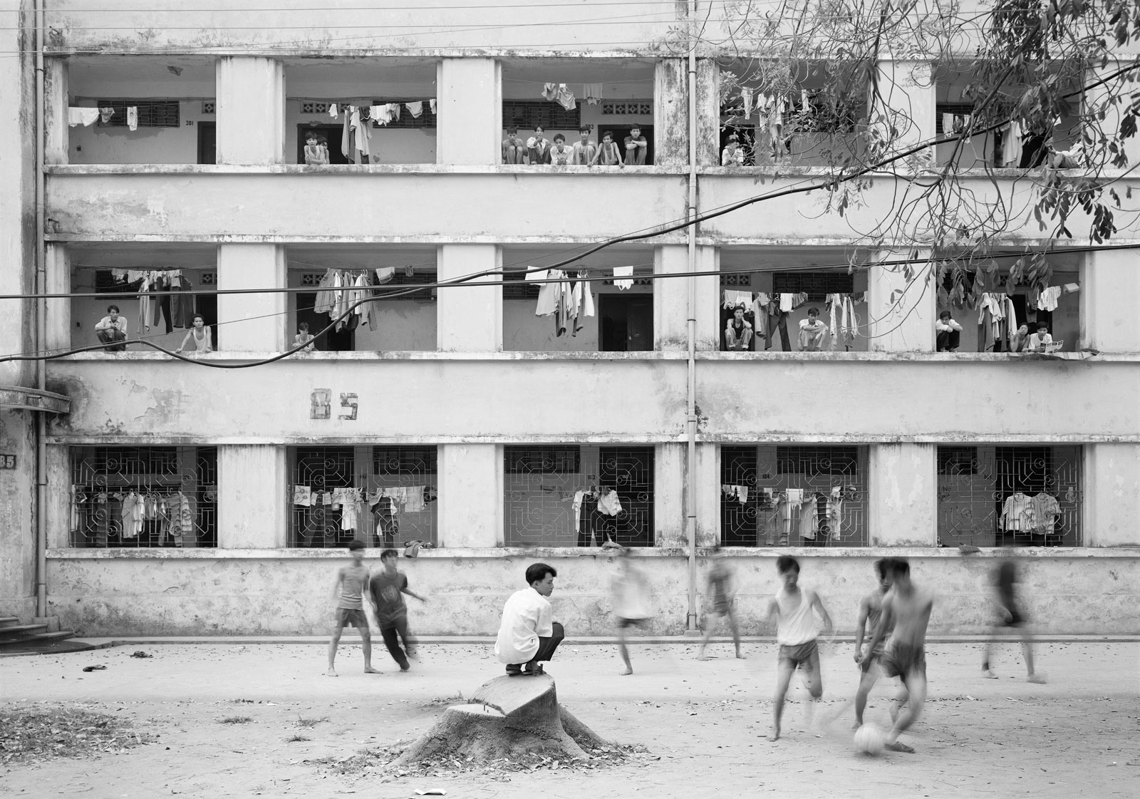 Kids playing outside an apartment complex, in black and white