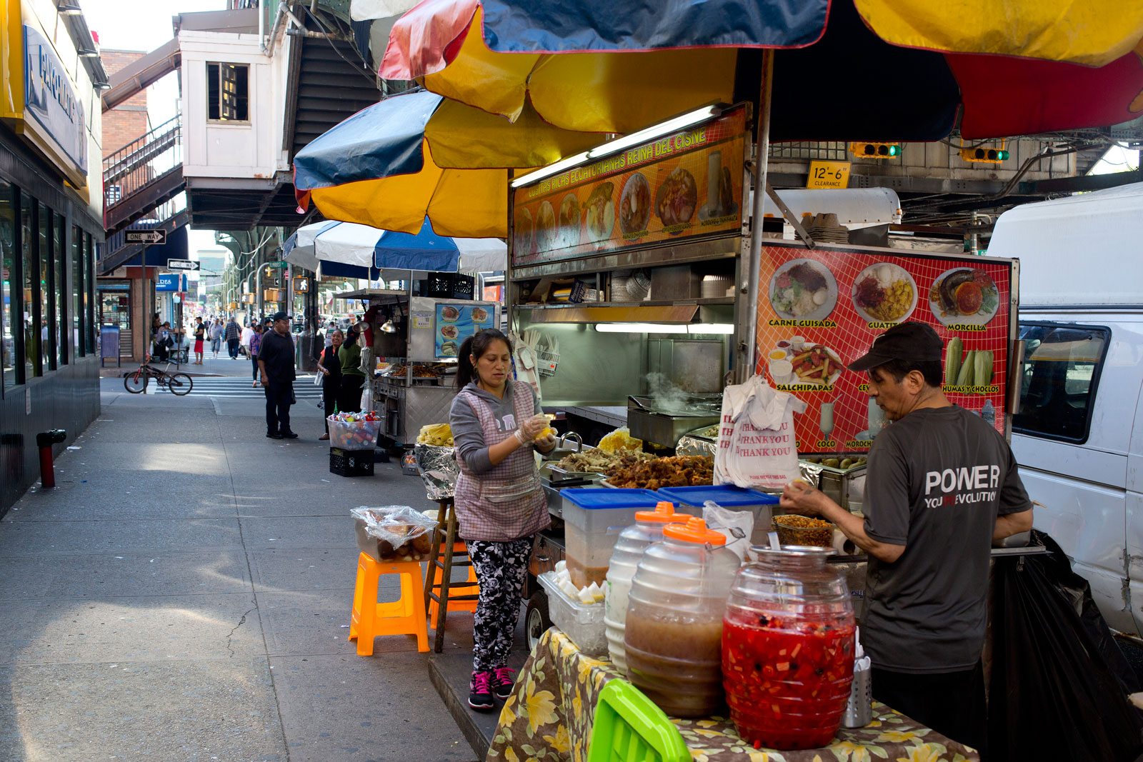 Two people selling food and drink from a cart on the side of a busy street