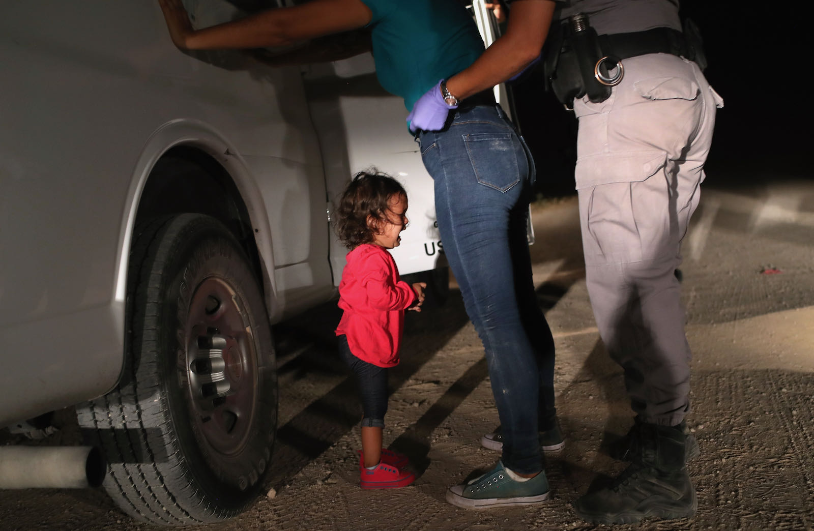 A two-year-old Honduran asylum-seeker crying as her mother is searched and detained near the US-Mexico border