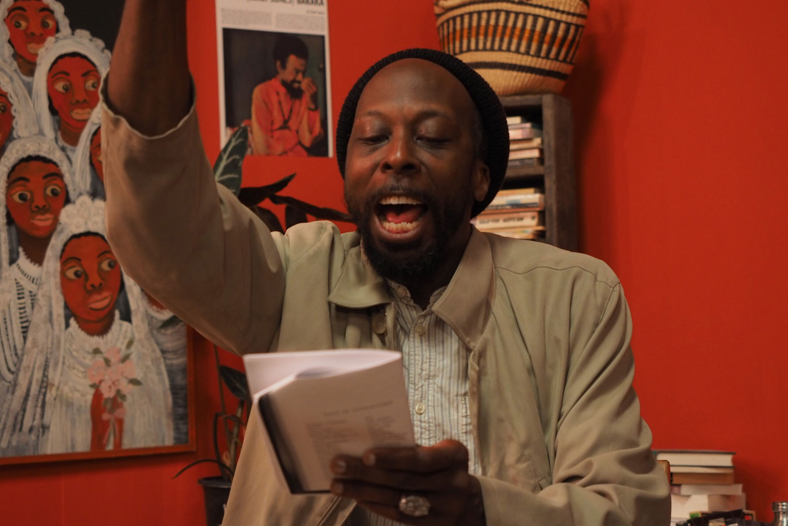 A black man reading from a text with his hand up in emphasis, before a red background
