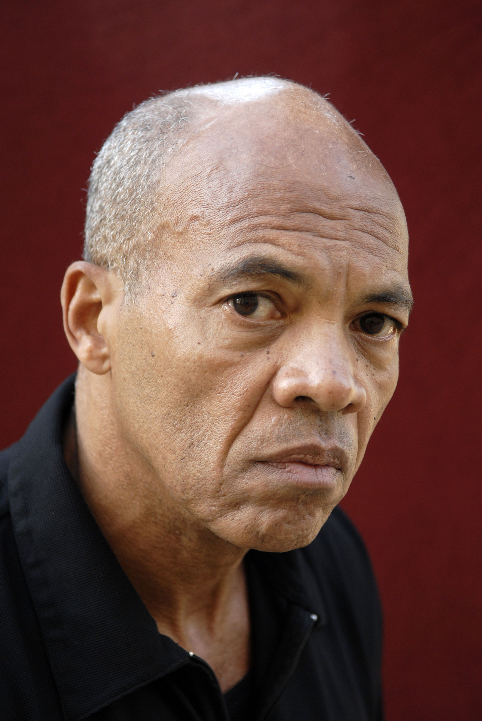 A close-up image of the writer John Edgar Wideman from the chest up in front of a red background