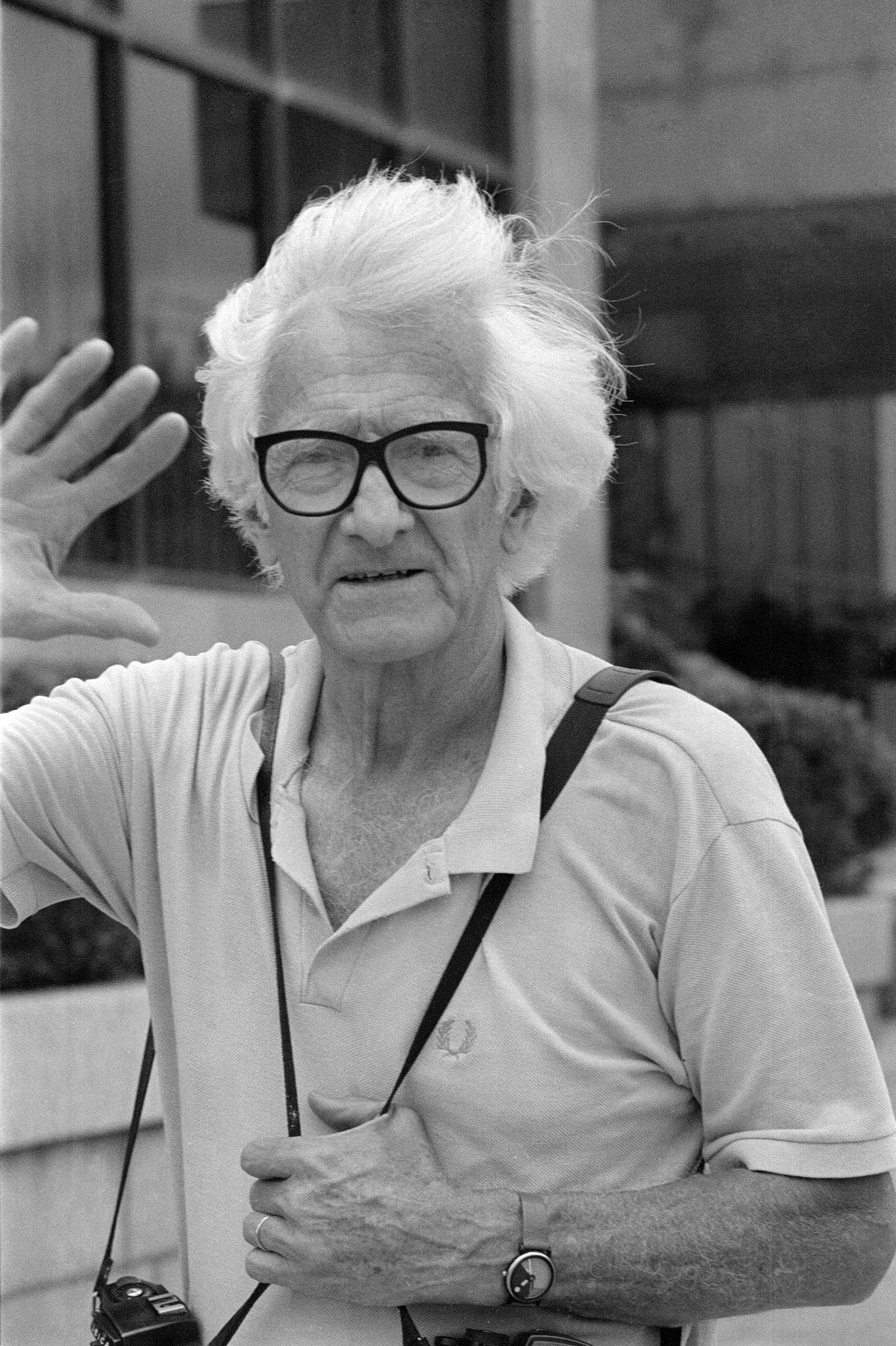 Marc Riboud, with white hair and black-rimmed glasses, waving with one hand up, the other holding the strap of the camera that hangs around his neck