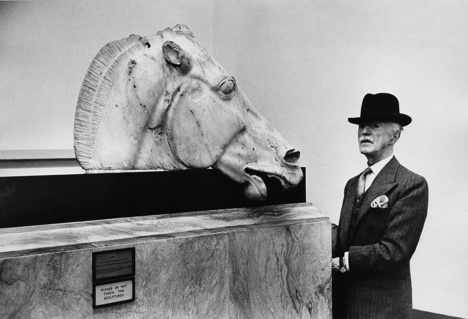 a man in a hat looking at a large horse head sculpture inside the museum