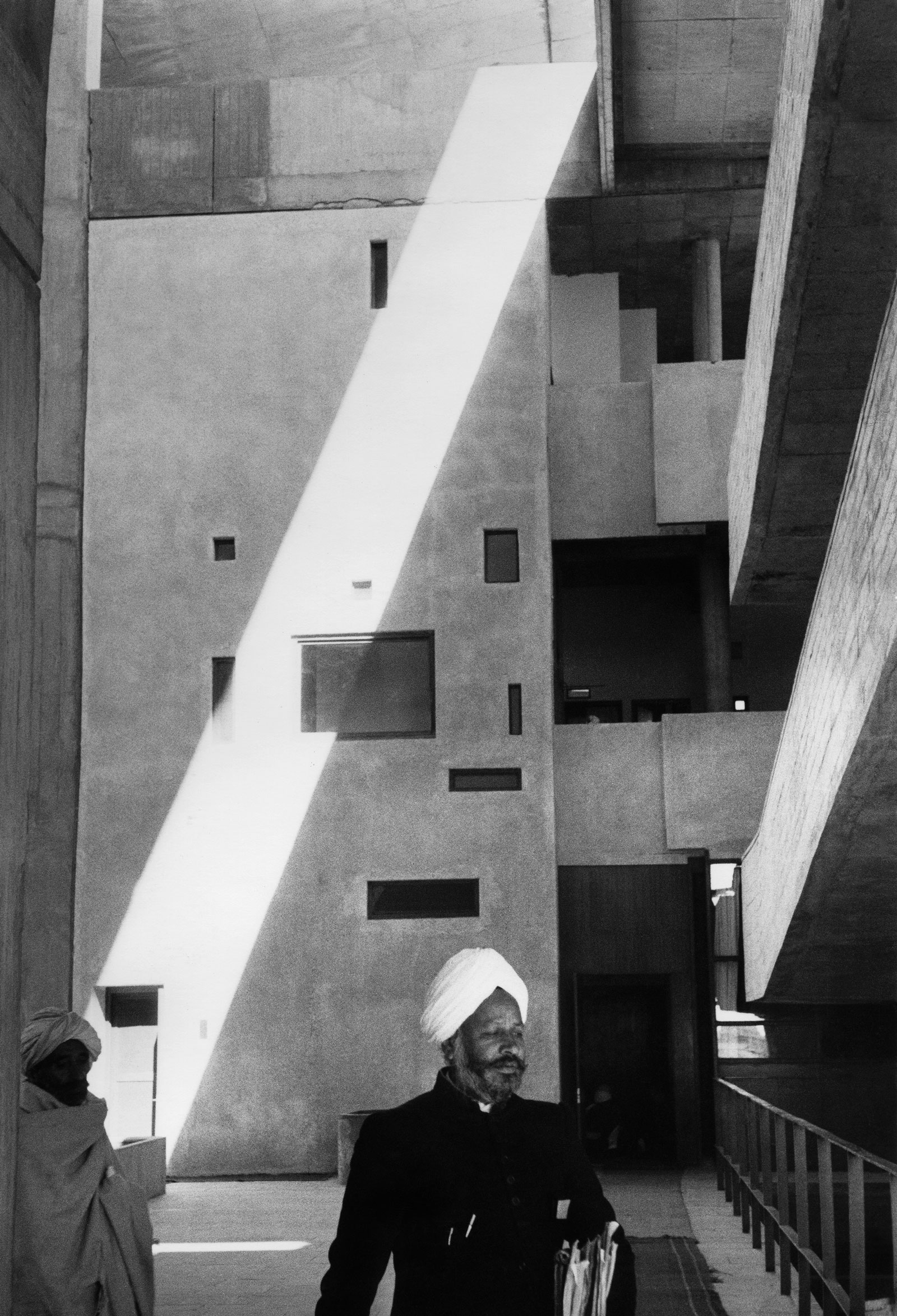 black and white shadows and geometries of the buildings in Chandigarh, with two figures include a man in a turban walking toward the camera