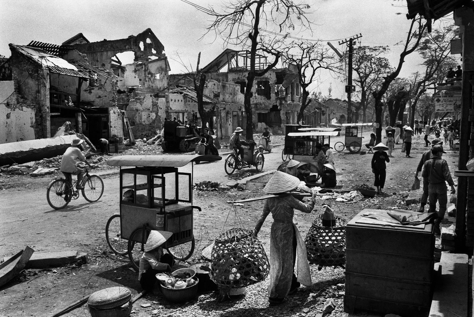 black and white image of the rubble in Hue, with people walking and bicycling, one woman in a hat carrying balanced bags over her shoulder