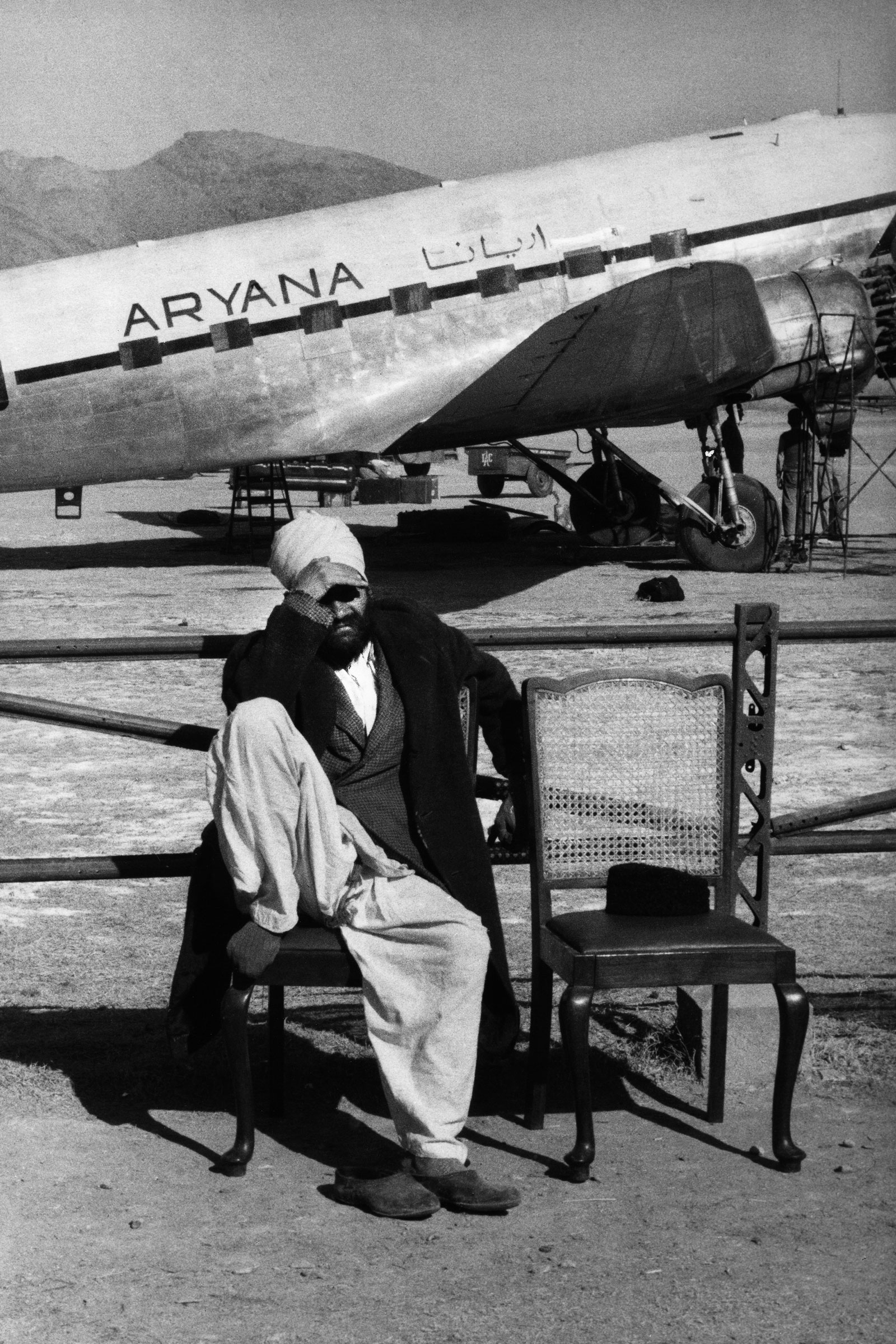 a man sitting on a chair in front of a plane, shields in face from the sun, in black and white