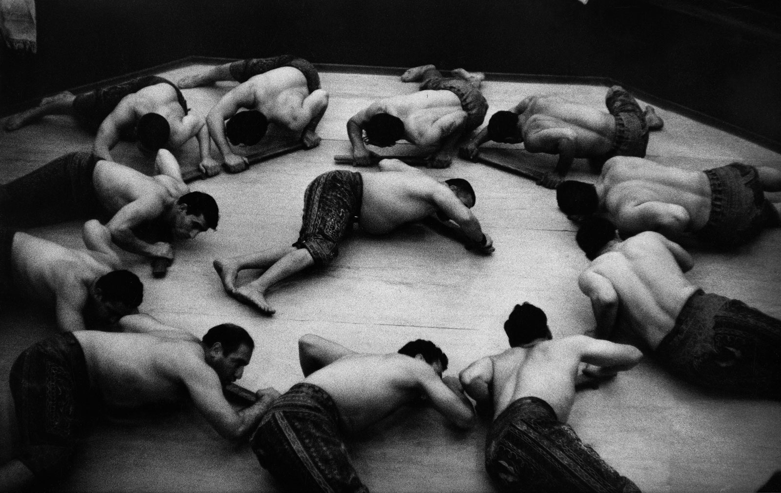 shirtless men lying on the ground form a circle, with one man in the middle, in black and white
