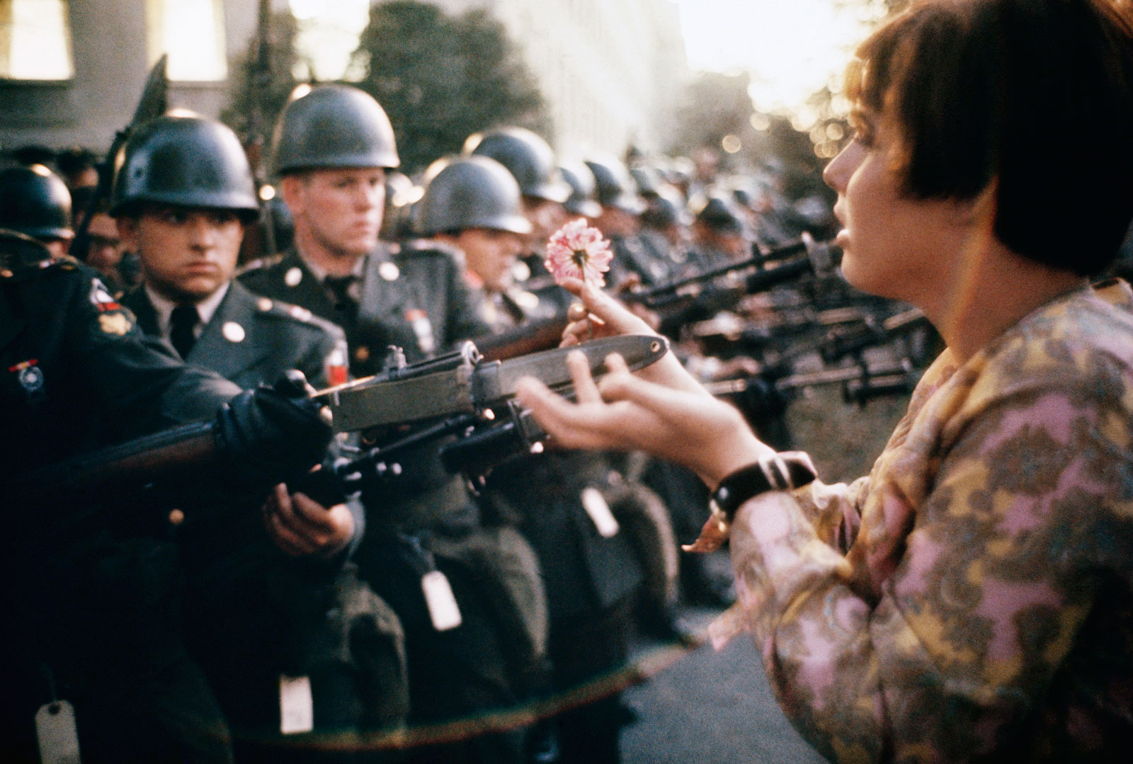 color image of a teenager holding a flower to the bayonets of police