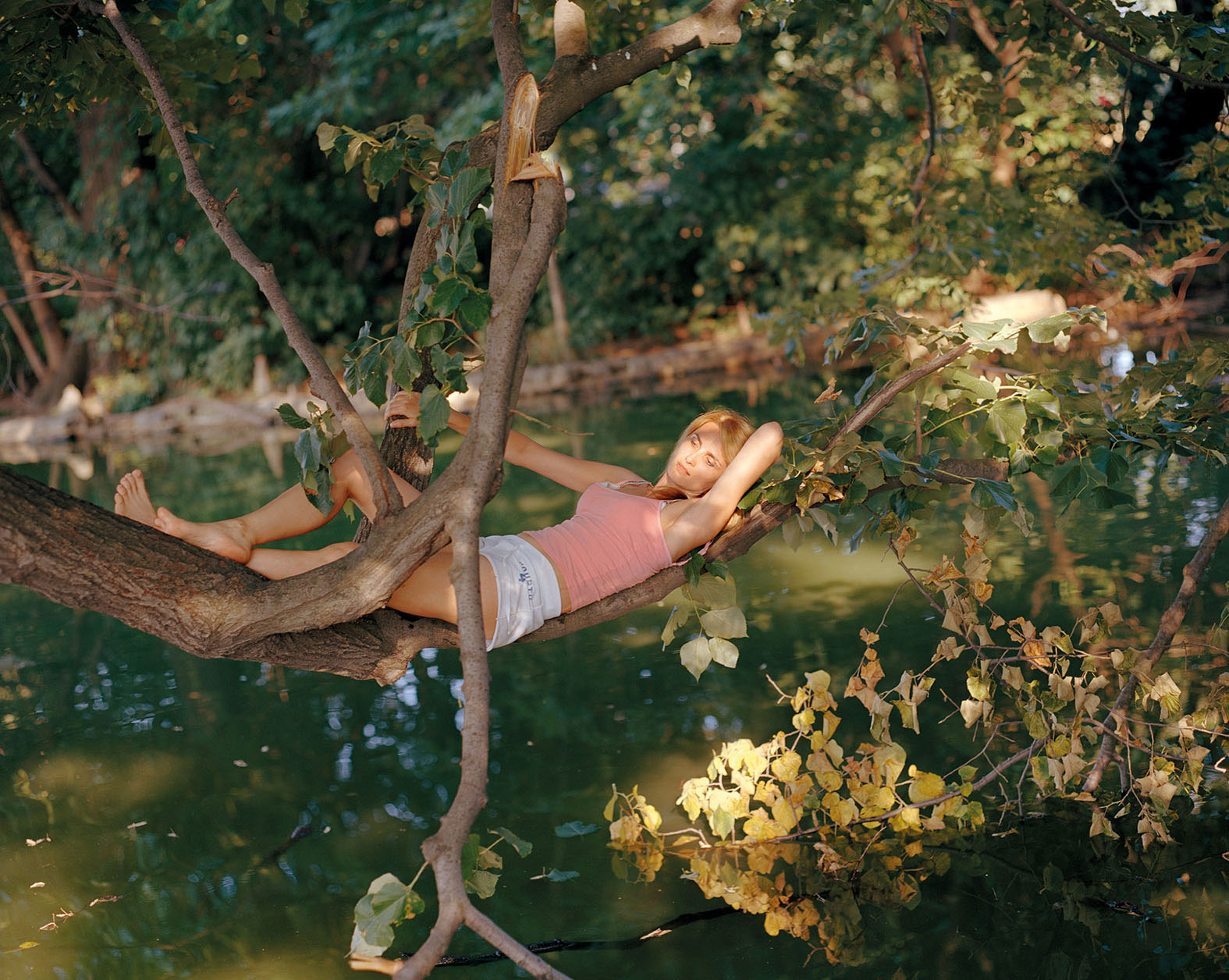 woman lying on a tree branch over water