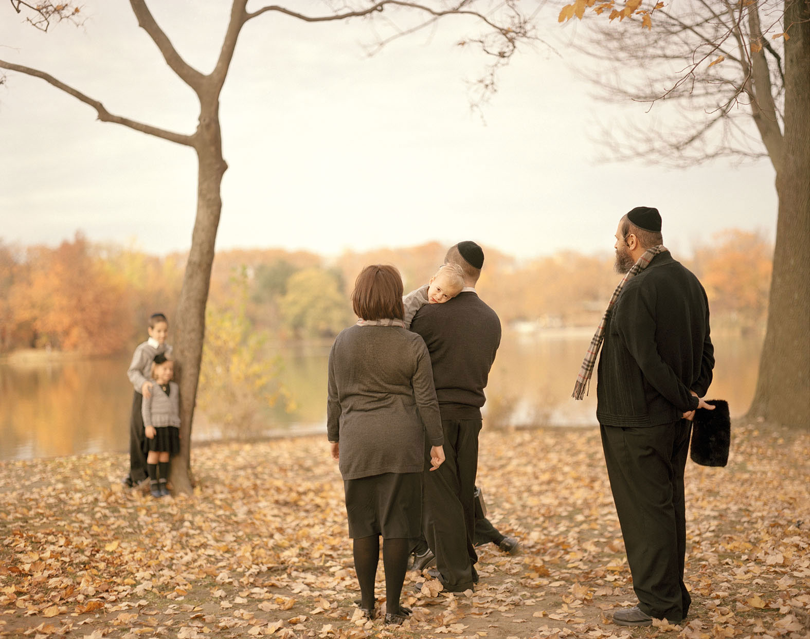 a Hasidic family stands, dressed nicely, on an autumn day, two children posed by a tree, three adults, one carrying a baby, looking on