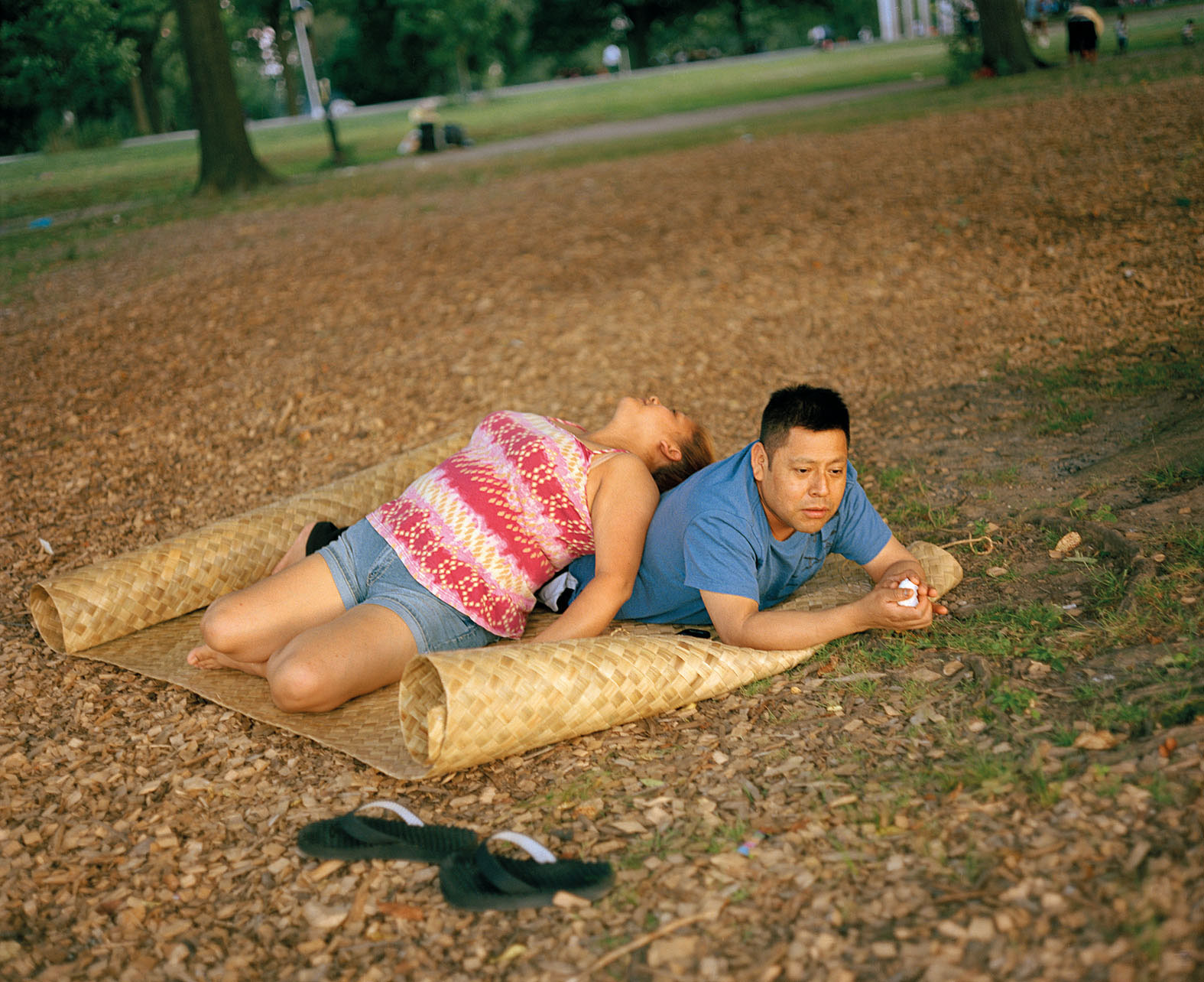 A woman leans against a man on a mat, lying down in the park