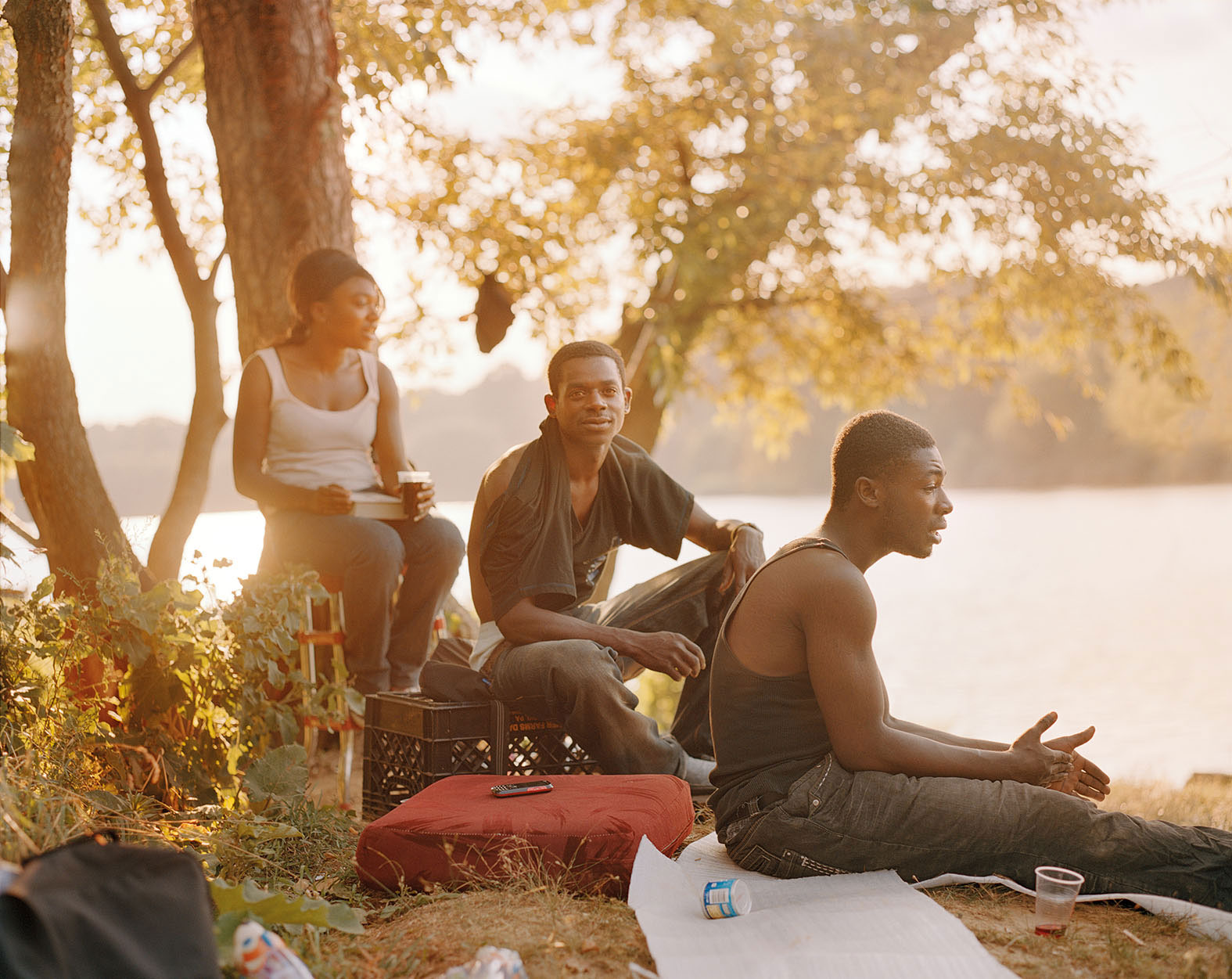 three African American figures, a woman and two men, sit near the lake, all awash in golden light and two men