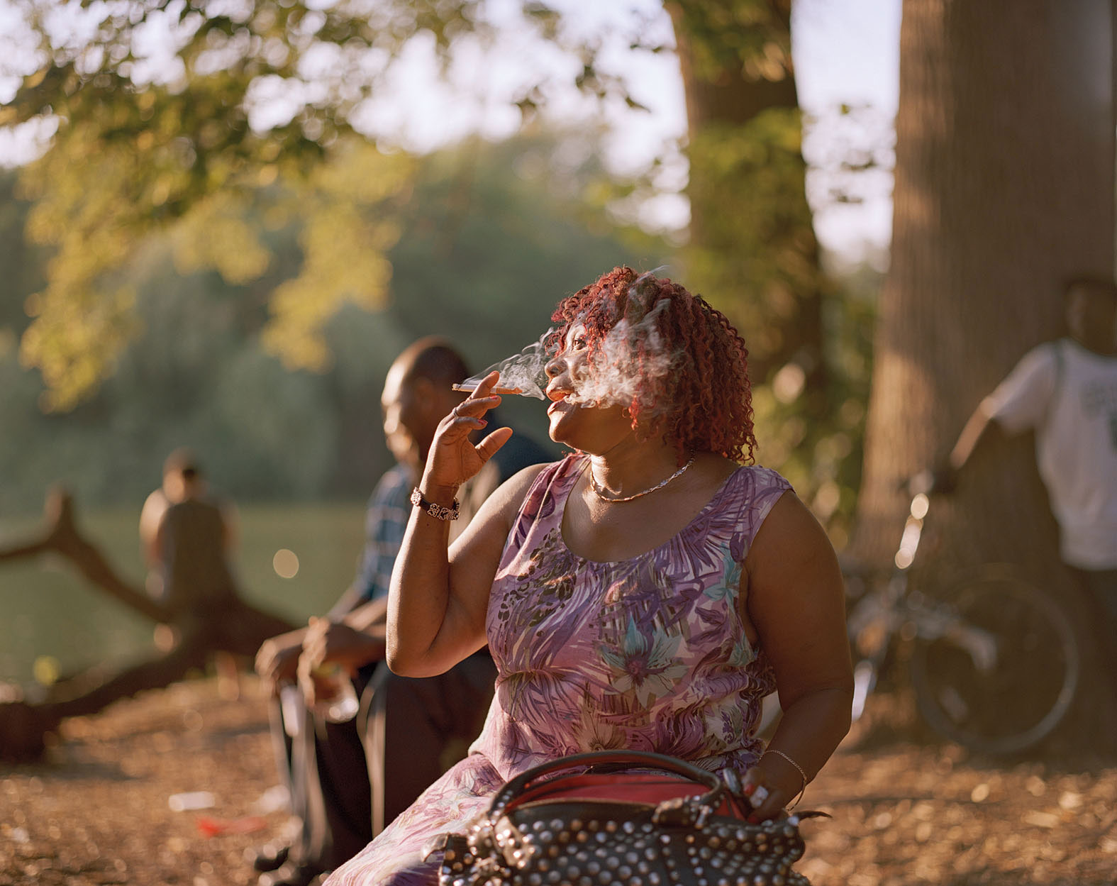 African American woman smoking with the sun against her, everything washed in golden light