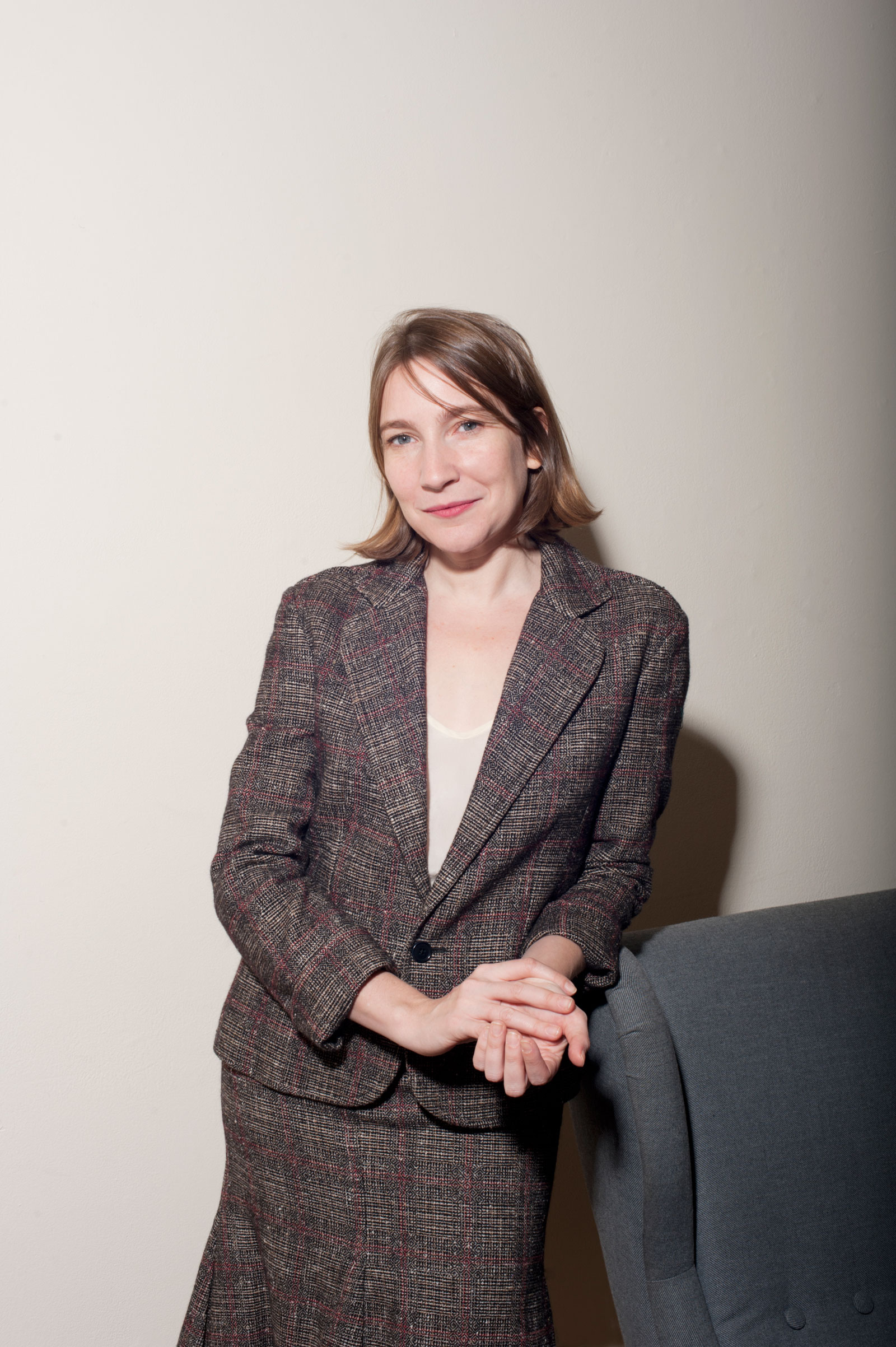 The smiling author in a gray skirt suit, standing and leaning on a blue chair
