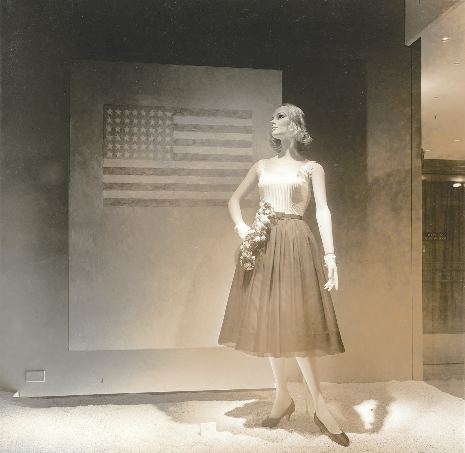 A window display at the Bonwit Teller department store featuring Flag on Orange Field (1957) by Jasper Johns, New York City, 1957