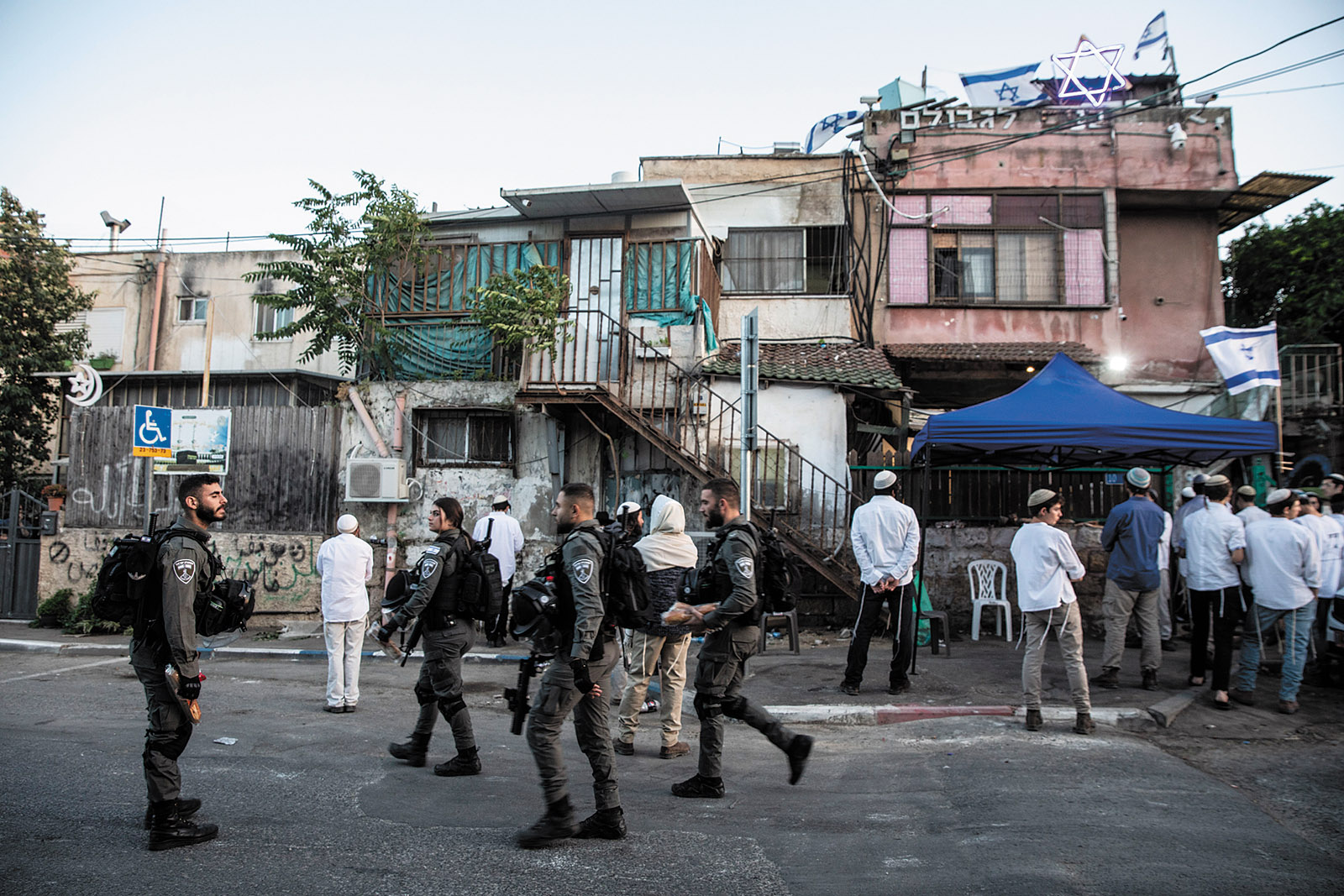 Israeli border police and settlers outside a residence that was taken over from a Palestinian family in the Sheikh Jarrah neighborhood of East Jerusalem